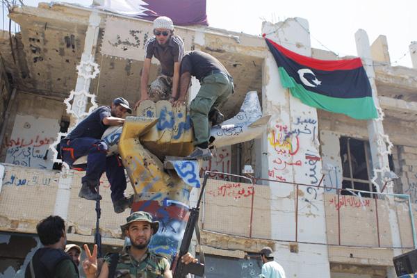 Enquanto luta se estende por Tripoli, insurgentes tentam localizar esconderijo de Kadafi. Presidente líbio usa rádio para convocar resistência