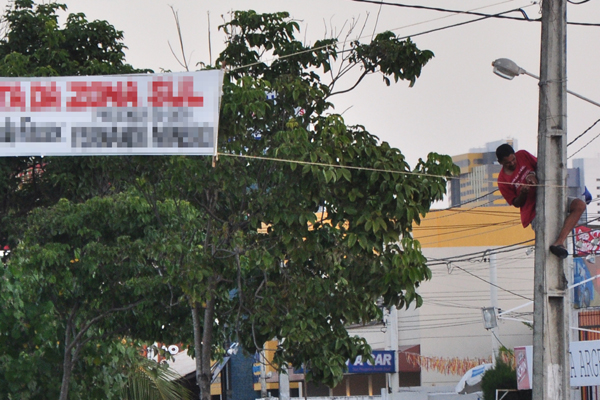 Na tarde de ontem, a equipe de reportagem da TRIBUNA DO NORTE flagrou um homem colocando tranquilamente mais uma faixa de propaganda irregular na av. Roberto Freire. Cena é comum no dia a dia da capital