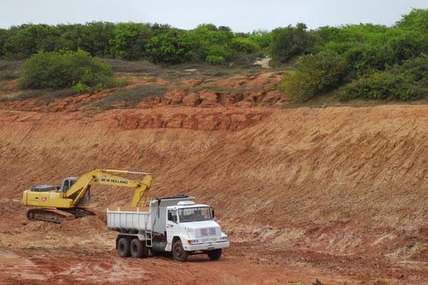 Máquina enchedeira da Construtora CLC coloca areia da APA de Jenipabu em cima de uma das cinco caçambas, que ontem à tarde, levaria o material para construção do Arena das Dunas.