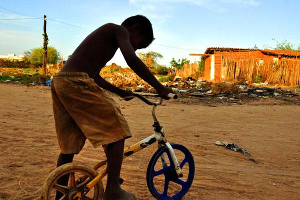 Garoto anda de bicicleta em rua de terra batida em uma das favelas de Mossoró, onde a renda é baixa e a infraestrutura deficiente