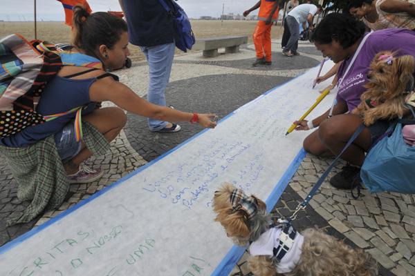 Moradores de Copacabana deixam mensagens sobre oceanos, em folha de papel com 150 metros