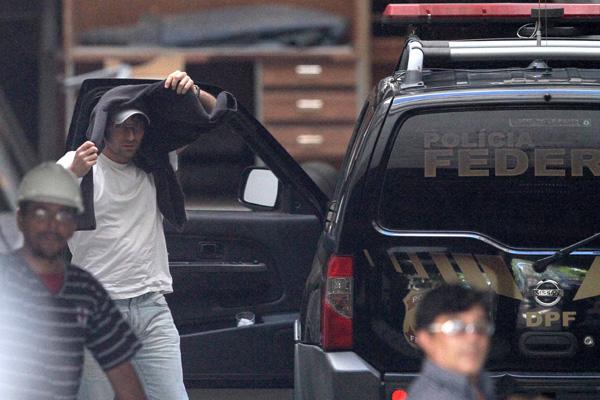 Rodrigo Vieira Emerenciano, o Mução tenta esconder o rosto quando era detido pela Polícia Federal no bairro Meireles, em Fortaleza