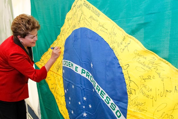 Na concentrao dos atletas brasileiros, a presidenta Dilma assina a bandeira que consta o nome de todos os membros da delegao nacional envolvida na disputa dos Jogos Olmpicos de Londres - 2012
