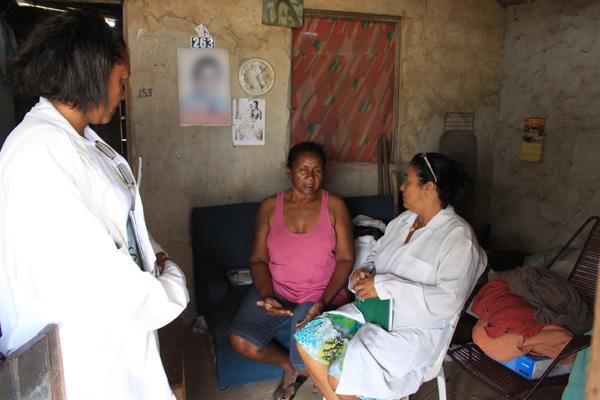 A costureira Maria Zélia, moradora da comunidade da África, recebe visita de enfermeiras do ESF e elogia atendimento